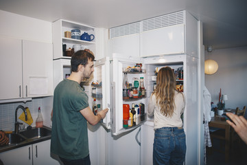 Man and woman standing by refrigerators in kitchen at college dorm