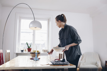 Side view of woman arranging plates on dining table at home
