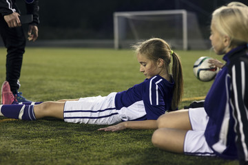 Low section of coach standing by girls relaxing on field against goal post