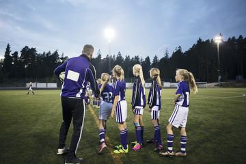 Coach explaining girls soccer team on field