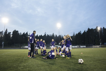 Coach standing by female soccer team on field against sky