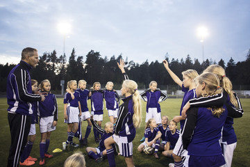 Coach standing with girls soccer team on field against sky