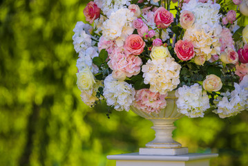 Vintage vase with roses and Hydrangea, eucalyptus bouquet outdoor on the grass