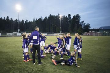 Coach explaining with girls soccer team on field against sky