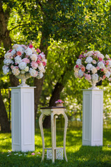 White antique vases with tenderness flowers and vintage table stand on the lawn grass in the garden. Wedding ceremony