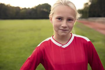Portrait of girl standing on soccer field