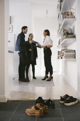 Various shoes on floor with female realtor discussing with young couple by shelves in background