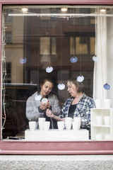 Female potters looking at ceramics container at store window