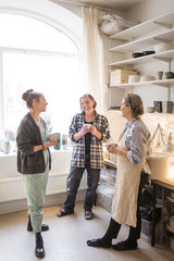 Happy female colleagues standing with coffee cups while talking at ceramics store