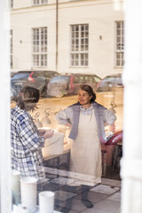 Happy female colleagues standing at ceramics store seen from window glass