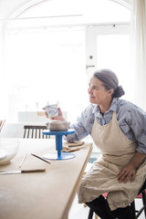 Smiling senior female potter holding ceramic vase while sitting at table in workshop