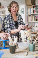 Mature female potter using mobile phone by senior colleague molding clay at workbench in store