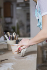 Midsection of female potter kneading clay on workbench at store