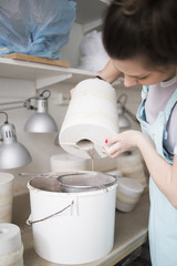 Young female potter pouring clay from vase in colander over bucket at workshop
