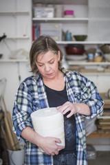 Mature female potter holding clay vase at workshop