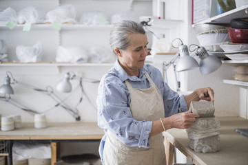 Senior female potter holding clay on table at workshop