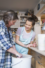 Happy woman looking at mature female potter mixing clay in bucket at store