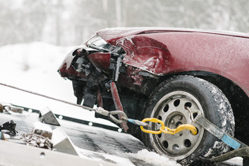 Damaged maroon car on tow truck during winter