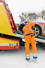 Rear view of driver attaching damaged car on tow truck during winter