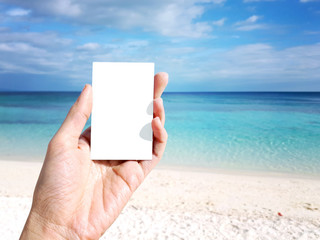 Hand of woman holding white blank paper note with beautiful cloud, blue sky over calm sea and fantastic white sand beach in background. Concept of environment background, copy space and clipping path.