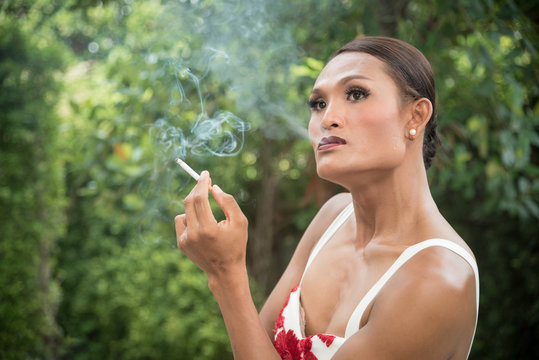 Portrait of Asian transwoman or transgender smoking cigarette in garden. People, smoking and bad habits concept. Picture for World No Tobacco Day.