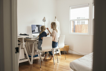 Rear view of design professional with daughter using computer at home
