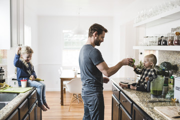 Girl looking at father feeding sister in kitchen at home