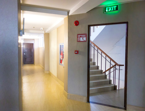 Building Emergency Exit with Exit Sign and Fire Extinguisher. stairwell fire escape in a modern building.