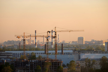 Photo of a building process in the city in the sunset. Cranes and pipes.