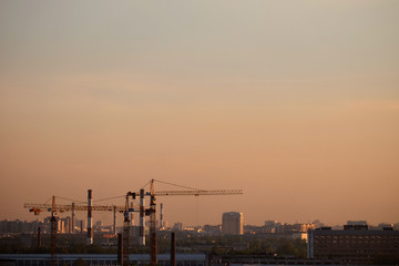 Photo of a building process in the city in the evening. Cranes and pipes.