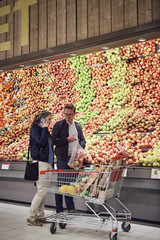 Man looking at woman talking on mobile phone while buying apples at supermarket