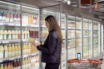 Side view of woman holding juice bottles at refrigerated section in supermarket