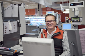 Portrait of smiling mature cashier sitting at checkout counter in supermarket