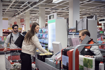 Man looking at woman paying to mature cashier in supermarket