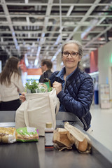 Portrait of woman holding groceries bag at checkout counter in supermarket