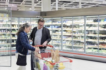 Man looking while woman keeping bottle in shopping cart at supermarket