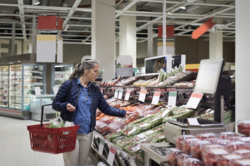 Mature woman buying at vegetables on display in supermarket