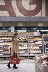 Side view of woman walking with basket by breads in rack at supermarket