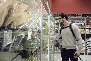 Man standing by flowers on display at supermarket