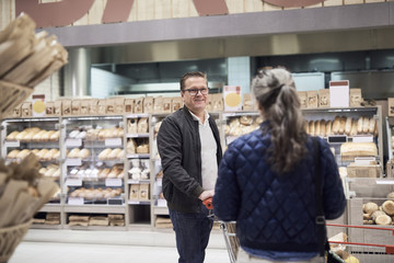 Couple talking while standing against bread rack at supermarket