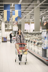Woman pushing shopping cart with groceries by cabinets at supermarket