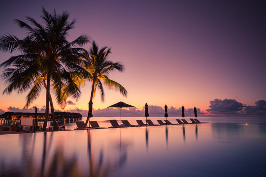 Luxury poolside on the beach with sunset colors. Amazing luxury summer background