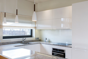 Modern kitchen design in light interior with wood accents. There is also a kitchen peninsula in the room. Kitchen and living room combined. European furniture, design, technologies.  Glamour design.