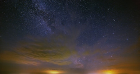 The stars of the Milky Way with clouds in the night sky.