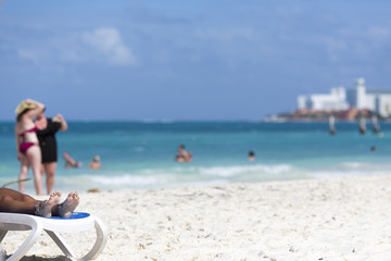 People on the beach on a sunny day. The Caribbean sea shore. Focus point on the toes in left. Copy space.