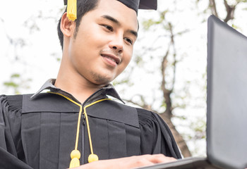 student graduate holding laptop computer with check job