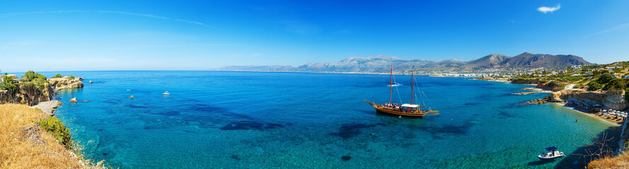 Panorama of beautiful scenery - traditional old fashioned cruise boat docked to the sand shore and colorful blue azure crystal clear water of Aegean Sea, Crete, Greece