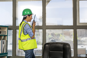 Female quarry worker standing in site office talking on radio device
