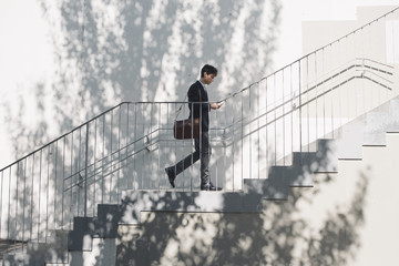 Young man in suit walking on stairs and looking at cell phone