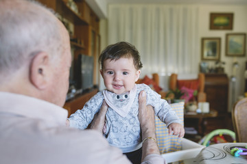 Great-grandfather holding a cute baby girl at home